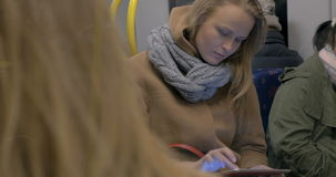 Young woman using tablet computer in subway train