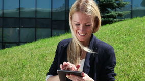 Young woman using a tablet computer. Young woman in suit using a tablet computer outdoor stock footage