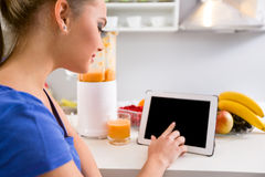 Young woman using tablet in kitchen Royalty Free Stock Images