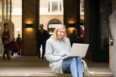 Young woman using tablet, laptop & mobile phone at the shopping Royalty Free Stock Photo