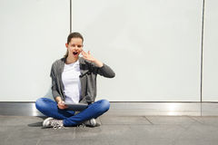 Young woman using tablet leaning to wall, very shock emotions over white wall Stock Photo