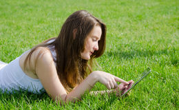Young woman using tablet notebook. Young woman or student lying on her stomach in the green grass using a tablet notebook Stock Photos