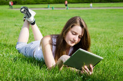 Young woman using tablet notebook. Young woman or student lying on her stomach in the green grass using a tablet notebook Royalty Free Stock Photo