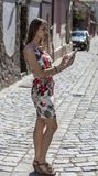 Young Woman Using a Tablet. Young woman is using a tablet in an old paved city street Royalty Free Stock Photography