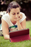 Young woman using tablet outdoor laying on grass royalty free stock images