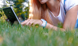 Young woman using tablet outdoor laying on grass Royalty Free Stock Image