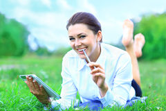 Young woman using tablet outdoor laying on grass Royalty Free Stock Photo