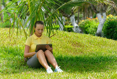 Young woman using tablet outdoor laying on grass. Royalty Free Stock Photography