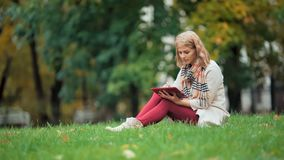 Young woman using tablet outdoor sitting on grass and smiling. Girl using digital tablet pc in the park. Student using tablet after school stock video
