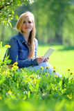Young woman using tablet in park Stock Photography