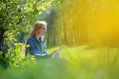 Young woman using tablet in park Royalty Free Stock Image