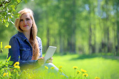 Young woman using tablet in park Royalty Free Stock Photography