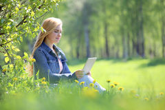 Young woman using tablet in park Royalty Free Stock Photo
