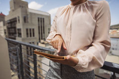 Young woman using tablet PC on balcony Royalty Free Stock Image