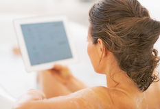 Young woman using tablet pc in bathtub. rear view Stock Image