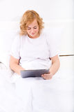 Young woman using a Tablet PC in bed Stock Photos