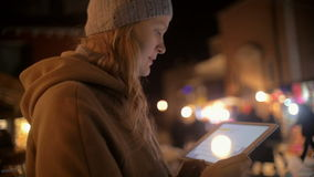 Young woman using tablet PC in the evening street. Slow motion of young woman with touch pad in the evening city.  She typing and sending message in chat stock video footage