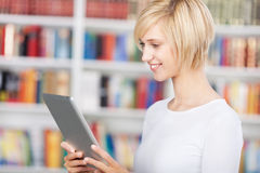 Young woman using tablet-pc in library. Smiling young woman using tablet-pc in library Stock Photo