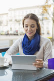 Young woman using tablet PC at sidewalk cafe Royalty Free Stock Photo