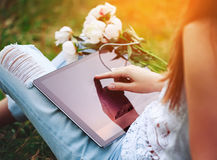 Young woman using a tablet pc sitting in summer grass with bouquet of peonies flowers. Royalty Free Stock Photos