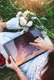 Young woman using a tablet pc sitting in summer grass with bouquet of peonies flowers. stock photography