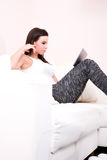 Young woman using a Tablet PC on the Sofa Royalty Free Stock Photography