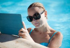 Young woman using a tablet poolside. Beautiful young woman wearing sunglasses using a tablet poolside resting her arms on the pool surround as she reads Royalty Free Stock Photo