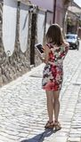 Young Woman Using a Tablet. Rear view of a young woman is using a tablet in an old paved city street Stock Images