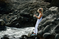 Young woman using tablet on rocky beach Royalty Free Stock Photography