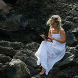 Young woman using tablet on rocky beach Royalty Free Stock Photos
