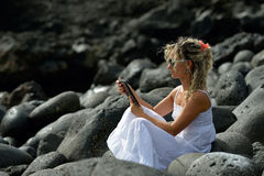 Young woman using tablet on rocky beach Stock Photography