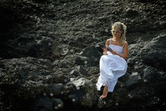 Young woman using tablet on rocky beach in summer Stock Photos