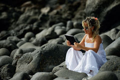 Young woman using tablet on rocky beach in summer Royalty Free Stock Photo