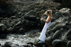 Young woman using tablet on rocky beach in summer Royalty Free Stock Images