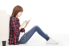 Young woman using tablet and sitting on the floor Stock Photo