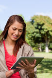 Young woman using a tablet while standing in bright park Stock Photography