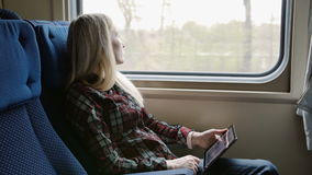 Young woman using tablet while traveling by train stock footage