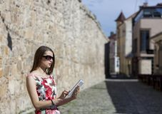 Young Woman Using a Tablet. Young woman is using a tablet in an old paved city street Royalty Free Stock Images