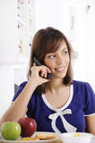 Young woman using telephone. In breakfast Royalty Free Stock Photography