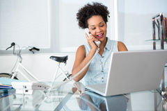 Young woman using telephone and laptop. Beautiful casual young woman using telephone and laptop in office Royalty Free Stock Photos