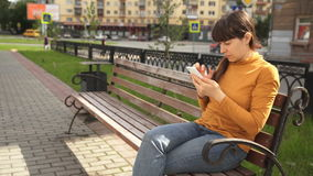 Young woman using telephone sitting on the bench near the road stock video