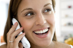 Young woman using telephone, smiling, close-up. Young women using telephone, smiling, close-up Royalty Free Stock Photos