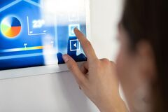 Young Woman Using The Home Automation System On Digital Tablet To Regulate The Temperature Stock Photography