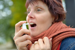 Young woman using throat spray. In cold season Stock Images