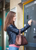 Young woman using ticket machine Royalty Free Stock Photography