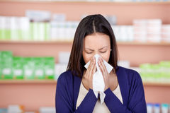 Young woman using tissue in pharmacy Royalty Free Stock Photography