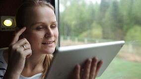 Young woman using touch pad sitting by the window stock video