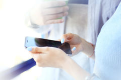 Young woman using a touchscreen smartphone. Royalty Free Stock Images