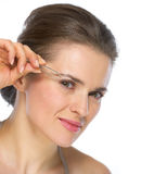 Young woman using tweezers on brow Stock Photography