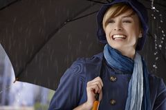Young woman using umbrella in rain Stock Images